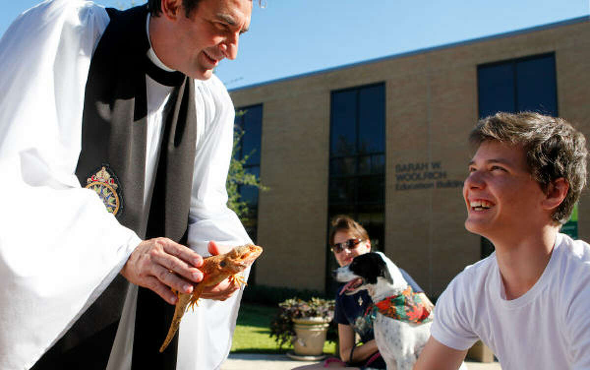 Father Stuart A. Bates blesses Raptor as owner, 17-year-old Alex Nunu, looks on during the annual Blessing of the Animals ceremony Sunday at St. Francis Episcopal Church in Houston. Nunu brought his 2-year-old bearded dragons siblings, Raptor and Saffron, to the ceremony.