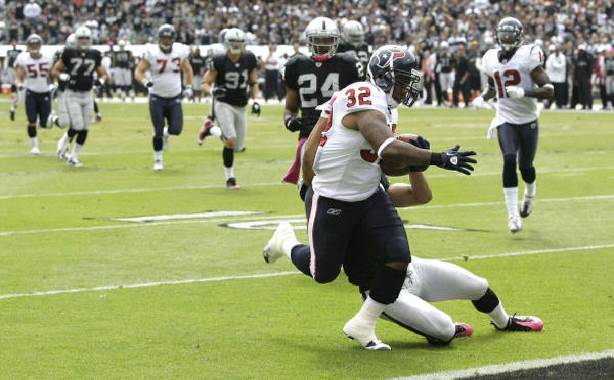 Texans running back Derrick Ward (32) dives toward the goal line while being hit by Raiders safety Tyvon Branch for a 33-yard touchdown run during the first quarter. Ward finished with 80 yards and a touchdown on 12 carries.