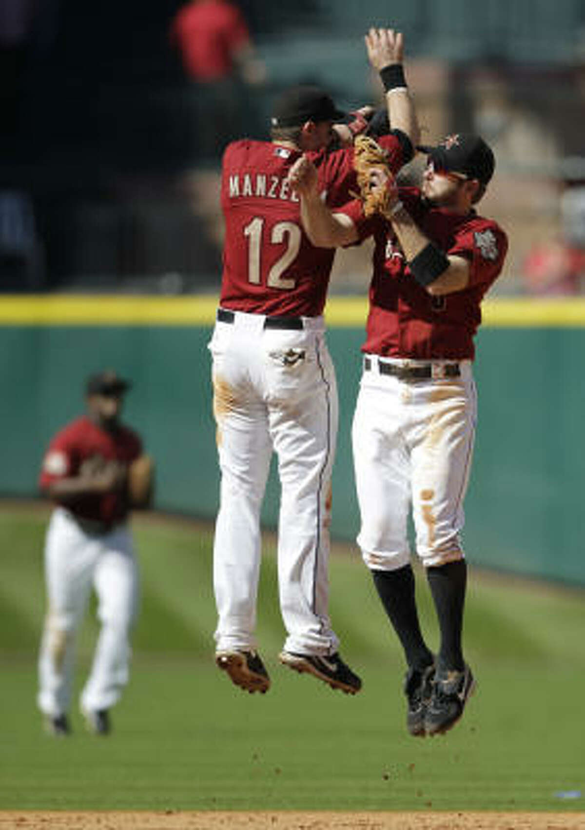 Tommy Manzella (12) and Jeff Keppinger celebrate their 4-0 win over the Chicago Cubs.
