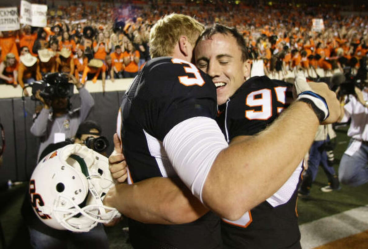 Oklahoma State quarterback Brandon Weeden (3) gives kicker Dan Bailey a hug after Bailey made the game-winning field goal to beat Texas A&M.