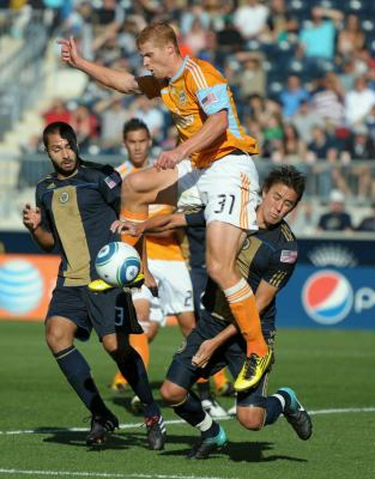 Dynamo defender Andrew Hainault deflects the ball in front of Philadelphia's Kyle Nakazawa. Hainault went on to score moments later.