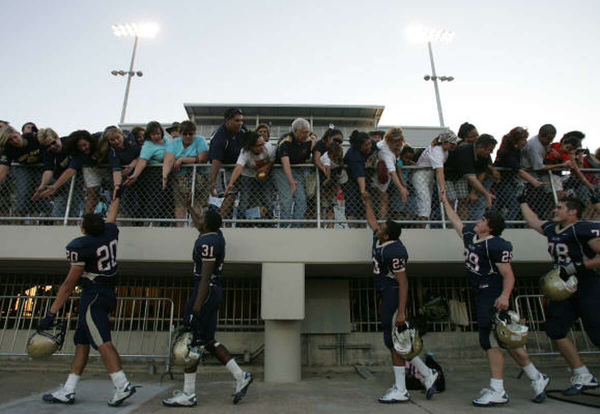 Klein Collins players celebrate their 28-21 victory over Dekaney with fans Saturday at Klein Memorial Stadium.
