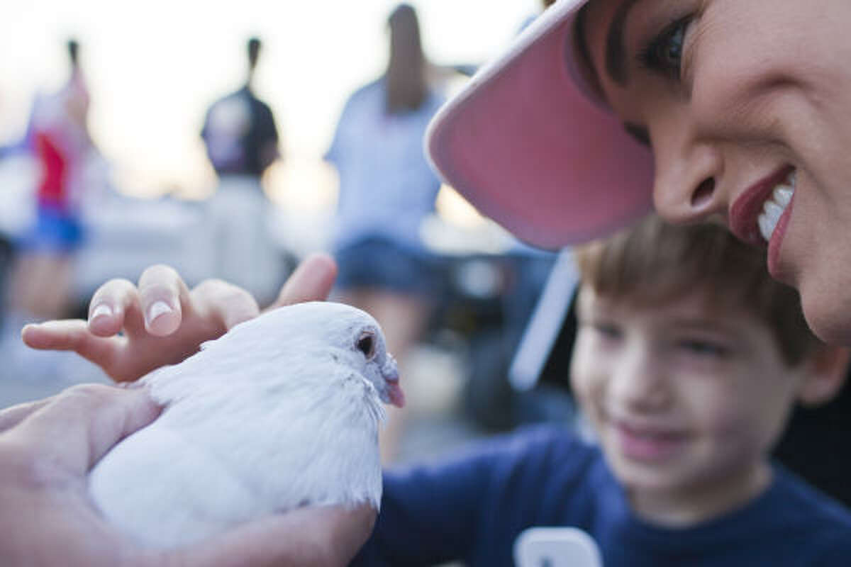 Melissa Wilson, right and son Zachary, 6, pet a dove before the begining of the Susan G. Komen Race for the Cure.