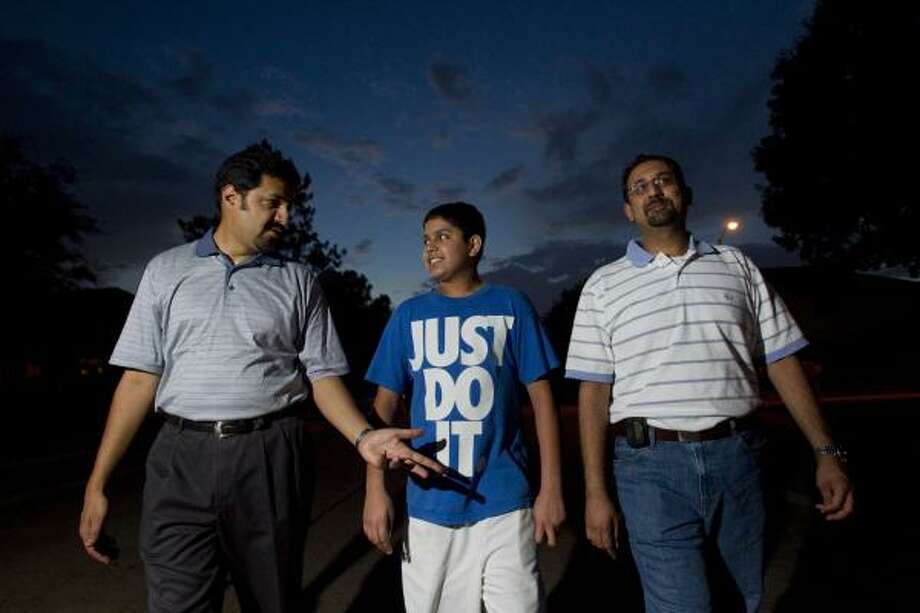 Nasir Malik, 43, Saqib Nasir, 14, and Ata Ahmad, 40, are among the group spreading a message of peace on a recent Saturday evening. Photo: Johnny Hanson, Houston Chronicle