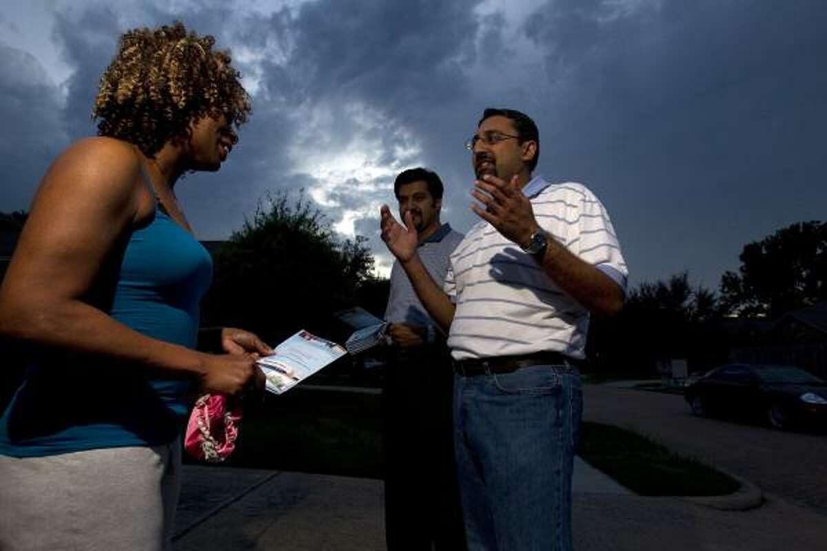 Ata Ahmad, 40, and Nasir Malik, 43, talk with Tish Bogany, a Christian, in north Houston.