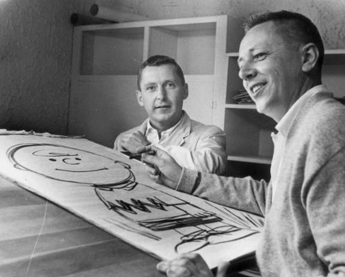 Here Charles Schulz, foreground, is shown with the real Charlie Brown, background, and a cartoon sketch of the comic strip character in this undated photo.