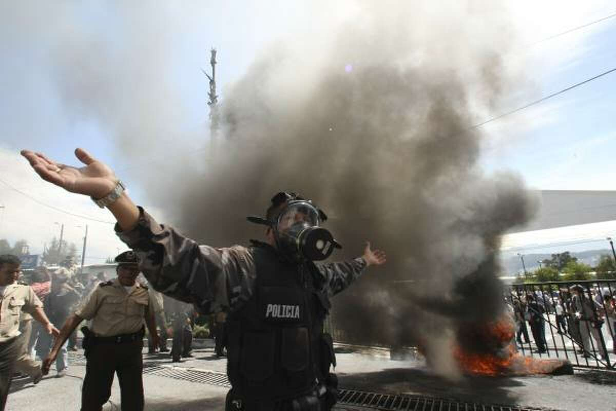 A police officer demonstrates next to a bonfire during a protest of police officers and soldiers against a new law that cuts their benefits at a police base in Quito, Ecuador, Thursday, Sept. 30, 2010. Hundreds of police protesting the new law plunged the country into chaos on Thursday, shutting down airports and blocking highways in a nationwide strike.