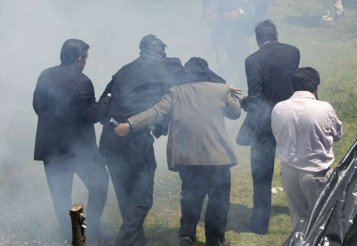 Wearing a gas mask, Ecuador's President Rafael Correa, second from left, back to camera, is helped as he runs away from tear gas during a protest of police officers and soldiers against a new law that cuts their benefits at a police base in Quito, Ecuador, Thursday, Sept. 30, 2010.