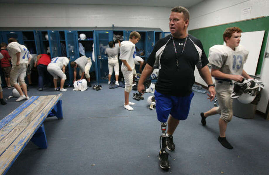 Nathan Potts instructs his team to get dressed and out to the field as soon as possible at the start of Tuesday's practice at Shepherd Middle School in Shepherd. Potts, a former assistant coach at Fort Worth Dunbar High School, coaches sub-varsity at Shepherd with former Dunbar coach Bob Jones. He left coaching to join the military after the terrorist attacks of 9/11 and had to have his leg amputated before returning to coaching. Photo: Julio Cortez, Chronicle