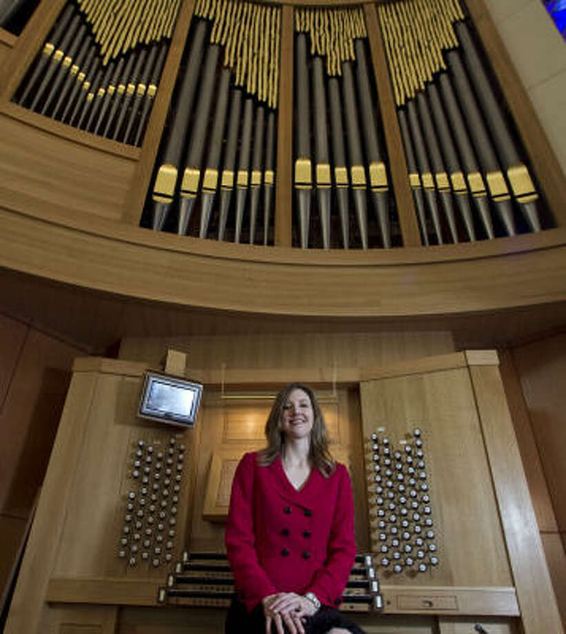 Organist Crista Miller poses for a portrait with the new pipe organ. Photo: James Nielsen, Chronicle