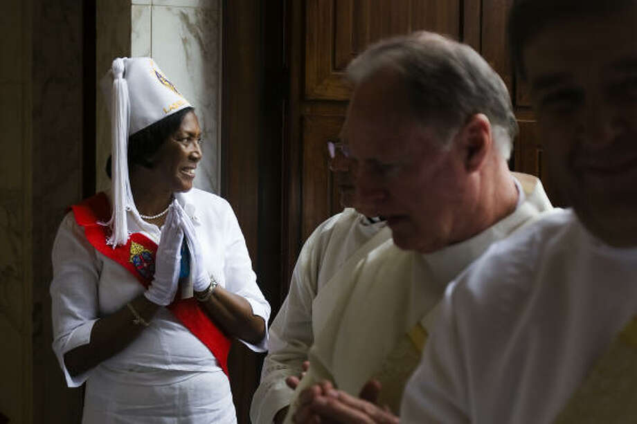 A member of the Knights of Peter Claver Ladies Auxiliary greets priests and deacons at the door. Photo: Smiley N. Pool, Chronicle