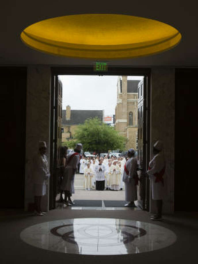 The procession of clergy arrives at the doors of the co-cathedral. Photo: Smiley N. Pool, Chronicle
