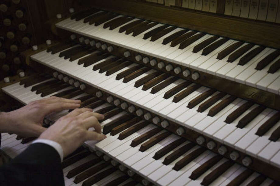 Gregory Hamilton plays the organ during the dedication. Photo: Smiley N. Pool, Chronicle
