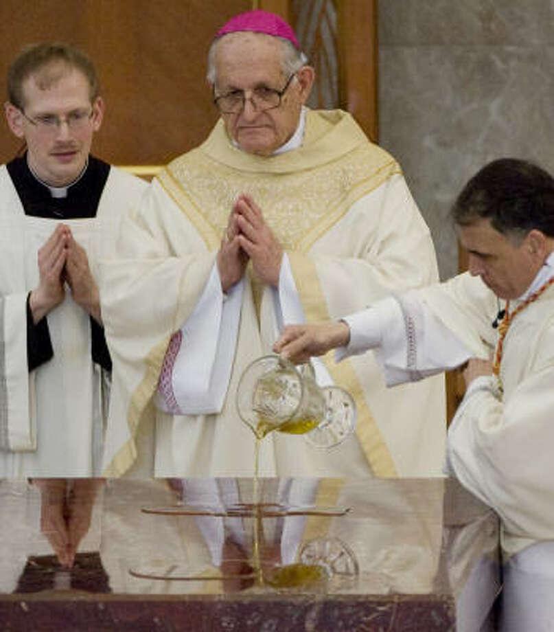 Archbishop Emeritus Joseph A. Fiorenza watches as Cardinal Daniel N. DiNardo anoints the altar with oil. Photo: Smiley N. Pool, Chronicle