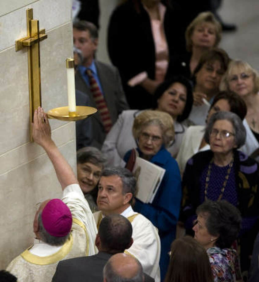 Retired Auxiliary Bishop Vincent M. Rizzotto anoints a cross on the wall of the nave. Photo: Smiley N. Pool, Chronicle