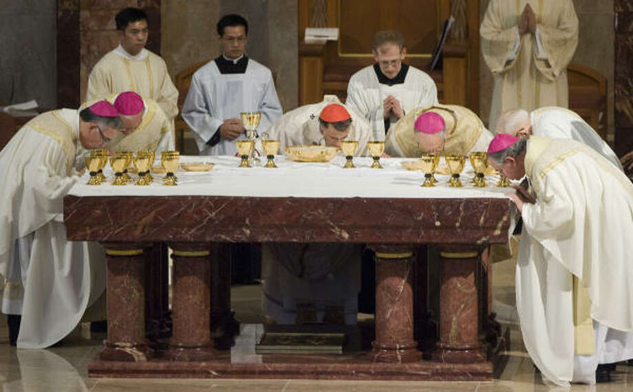 Cardinal Daniel N. DiNardo, center, kisses the altar with, from left, Auxiliary Bishop Joe S. Vasquez, retired Auxiliary Bishop Vincent M. Rizzotto,  Archbishop Emeritus Joseph A. Fiorenza, the Rev. Larry Lee (most senior Galveston-Houston priest) and San Antonio Archbishop  Jose H. Gomez. Photo: Smiley N. Pool, Chronicle