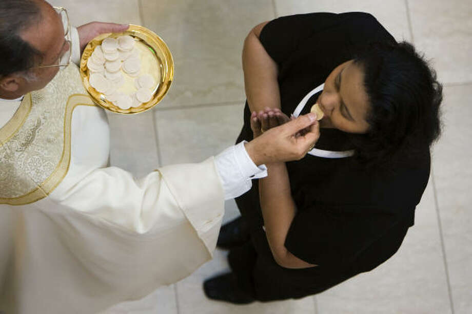 A worshipper receives communion. Photo: Smiley N. Pool, Chronicle