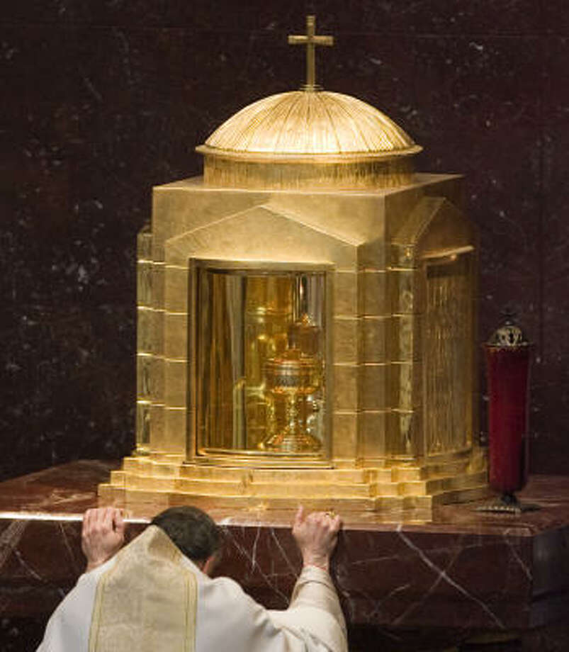 Cardinal Daniel N. DiNardo kneels before the tabernacle in the Chapel of the Blessed Sacrament. Photo: Smiley N. Pool, Chronicle