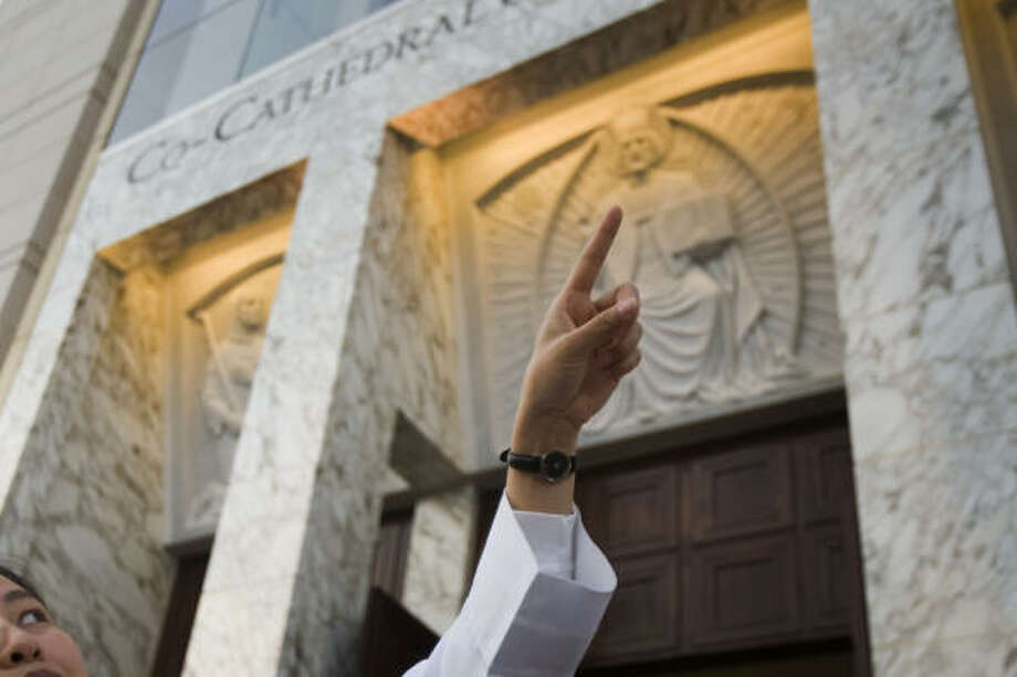 A nun points up at details above the doors of the Sacred Heart Co-Cathedral. Photo: Smiley N. Pool, Chronicle