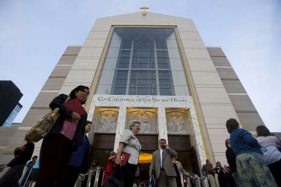 Worshippers leave the building following First Vespers at the Sacred Heart Co-Cathedral.  The service was the first in the new building, which will be dedicated with services on Wednesday. Photo: Smiley N. Pool, Chronicle