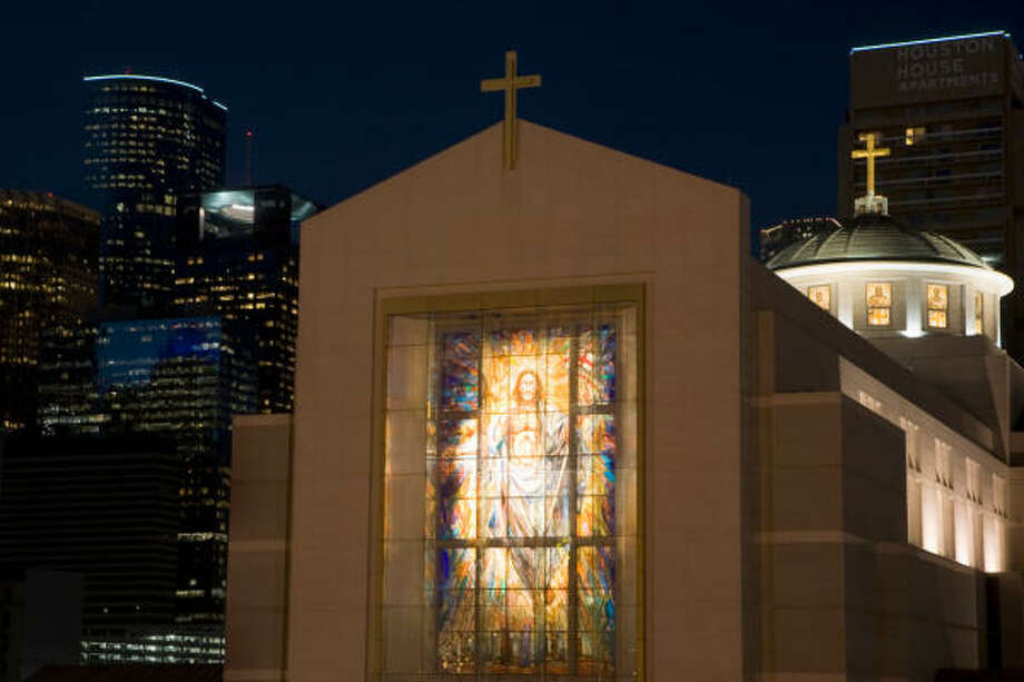 The Resurrection Window, a 40-foot-tall stained-glass window on the facade of the cathedral, is illuminated as dusk falls on the Co-Cathedral of the Sacred Heart in downtown Houston. Photo: Smiley N. Pool, Chronicle