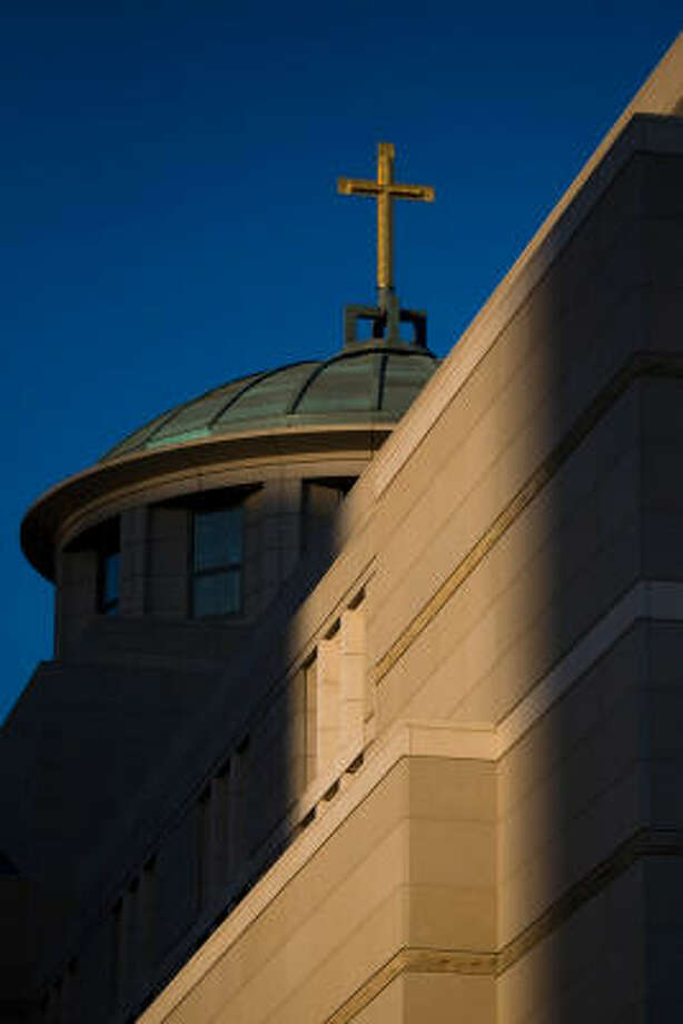 Evening sunshine illuminates the cross on top of the Co-Cathedral of the Sacred Heart. Photo: Smiley N. Pool, Chronicle