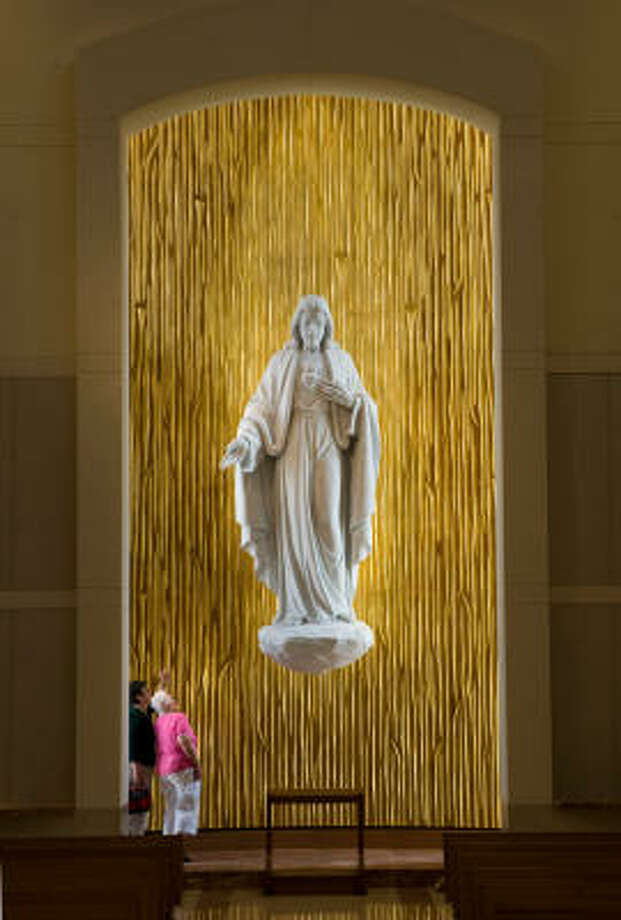 Two visitors take preview look at the Sacred Heart of Jesus, a 12-foot sculpture of white Carrara marble. Photo: Smiley N. Pool, Chronicle