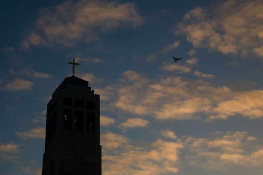 Just as the sun rises, a bird flies past the bell tower. Photo: Smiley N. Pool, Chronicle