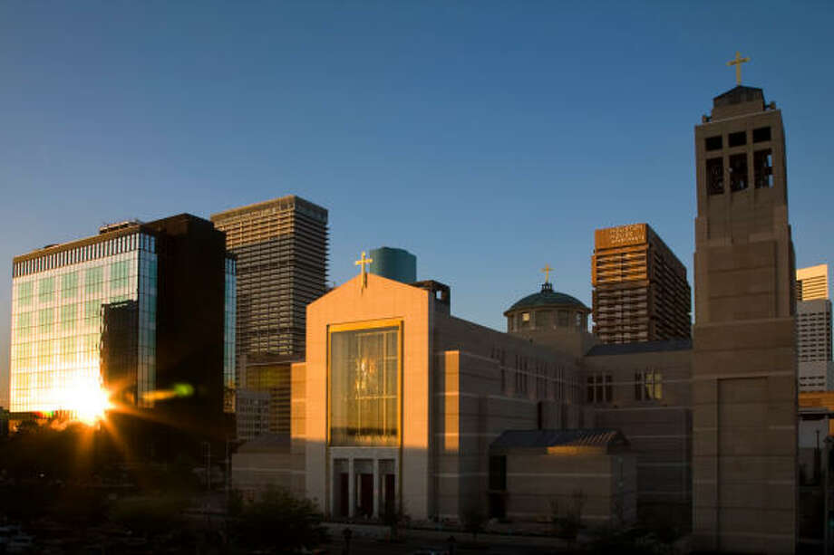The setting sun illuminates the Co-Cathedral of the Sacred Heart and the downtown skyline. Photo: Smiley N. Pool, Chronicle