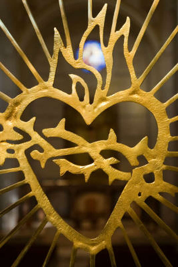 Iron work in the railing of the choir loft symbolizes the sacred heart. Photo: Smiley N. Pool, Chronicle