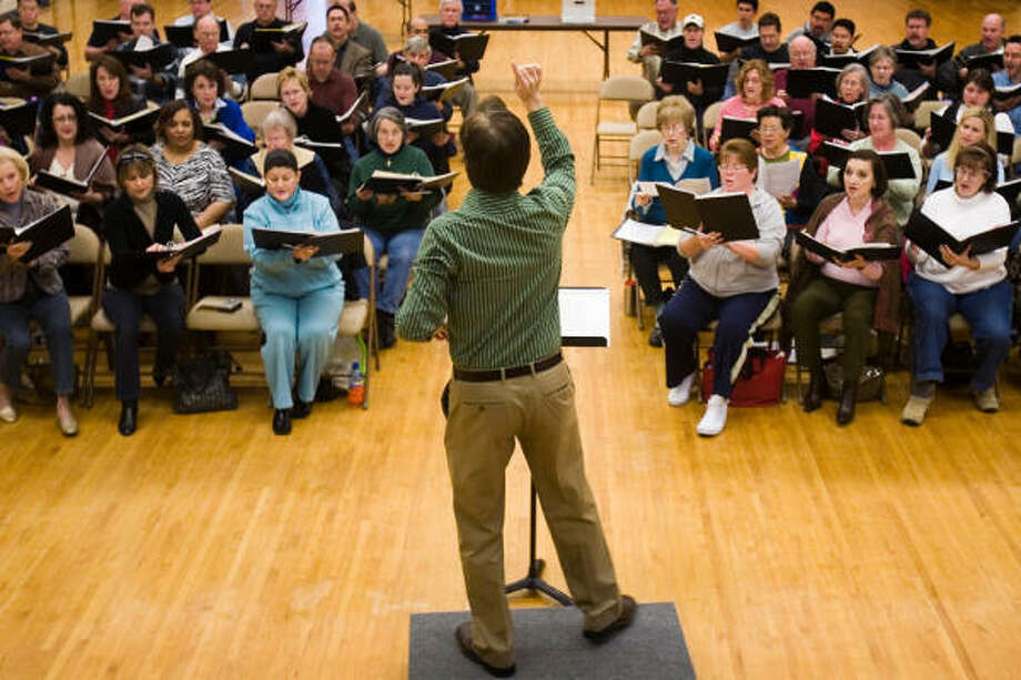 Kevin Klotz conducts a rehearsal for a choir that will perform at the opening of the Co-Cathedral of the Sacred Heart. Photo: Smiley N. Pool, Chronicle