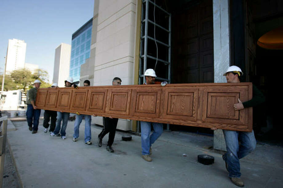 Sheldon Stevenson, right, looks back as a group of men carry a wood panel for the pews of the Co-Cathedral of the Sacred Heart. Photo: Julio Cortez, Houston Chronicle