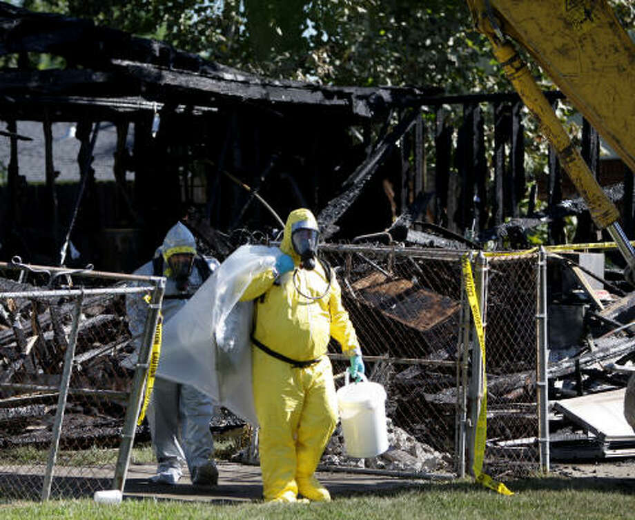 """Members of the Methamphetamine Initiative Group gather evidence after looking through the debris of a garage at 10711 Donegal Way, that caught on fire, late last night, as they look for clues, Wednesday, Sept. 29, 2010, in Houston. """"Because of the chemicals we are dealing with, we thought we needed to be very careful,"""" said Robert Koryciak with the Houston Fire Department Arson Bureau. """"Not only are they very dangerous to health, they are very volatile and explosive."""" Photo: Karen Warren, Chronicle"""