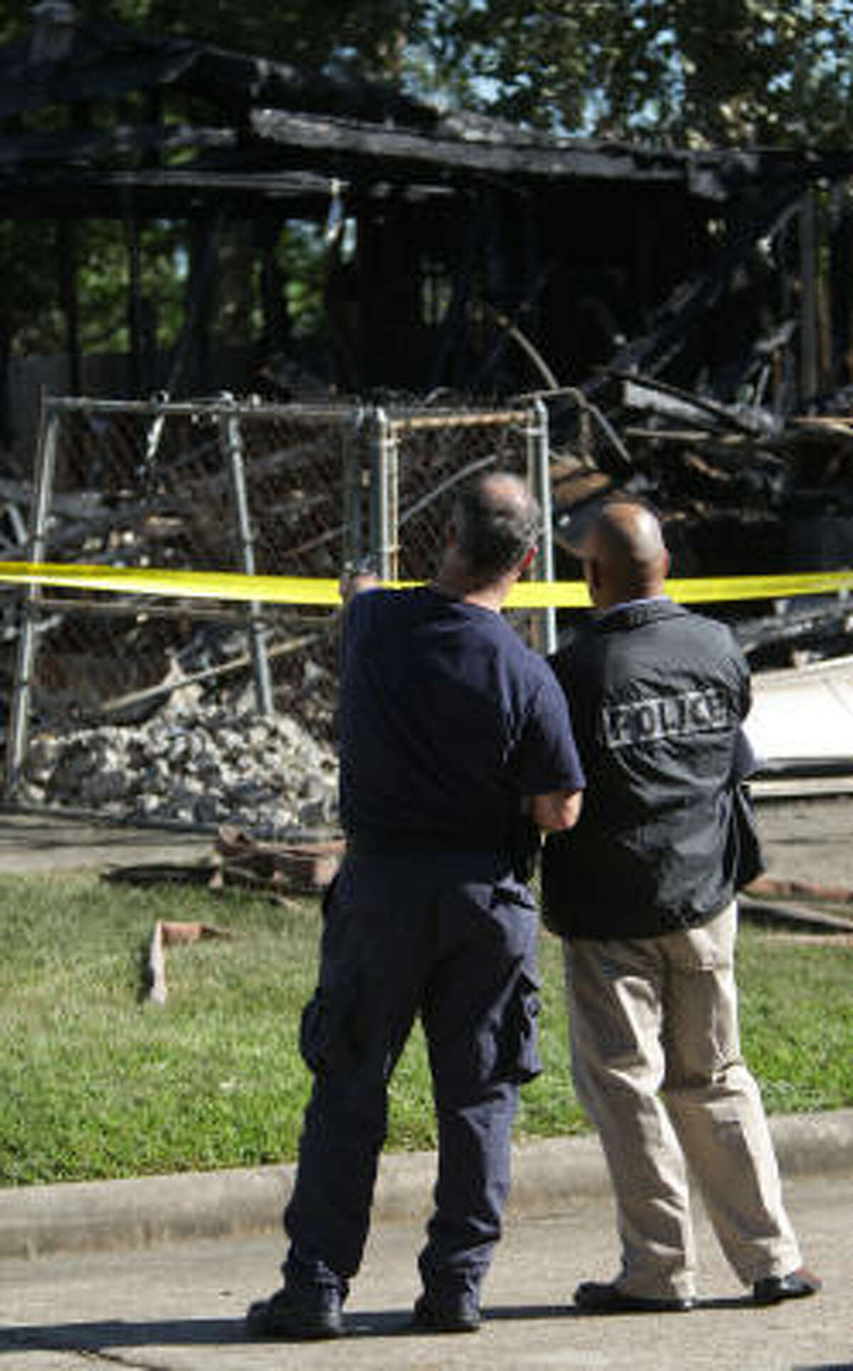 Officials look on as members of the Methamphetamine Initiative Group sift through the debris of a garage at 10711 Donegal Way, that caught on fire, late last night, as they look for evidence, Wednesday, Sept. 29, 2010, in Houston.
