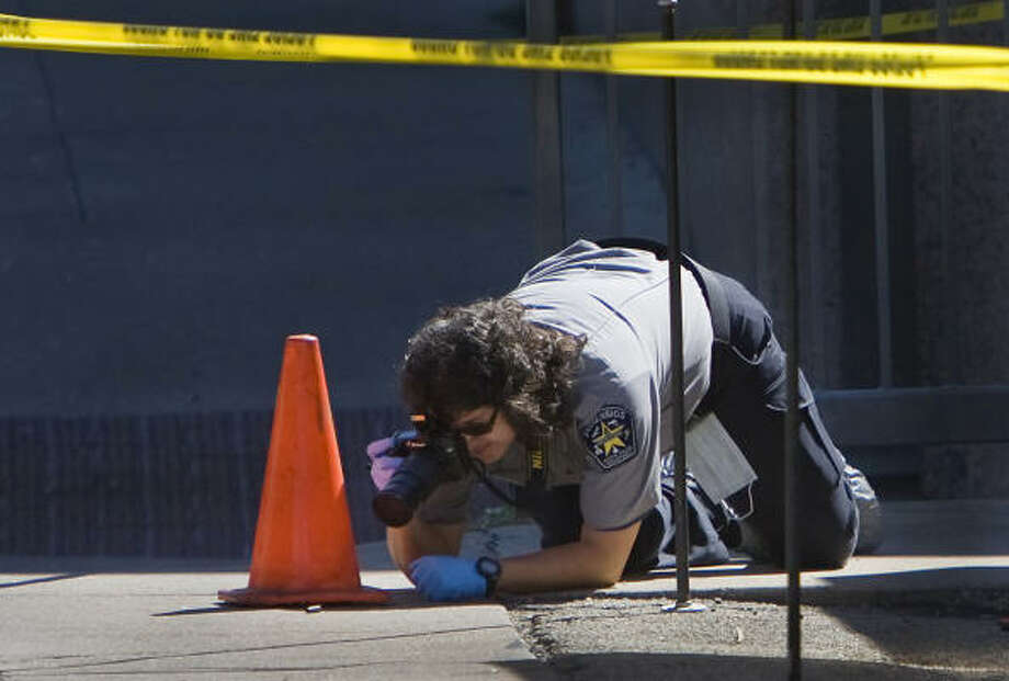 An Austin Police Department forensics worker takes a picture of a empty shell casing along 21st Street just west of Whitis in front of the Catholic church on the University of Texas campus in Austin along the path a gunman reportedly took on his way to the Perry-Castaneda Library where he fatally shot himself. Photo: Ralph Barrera, AP