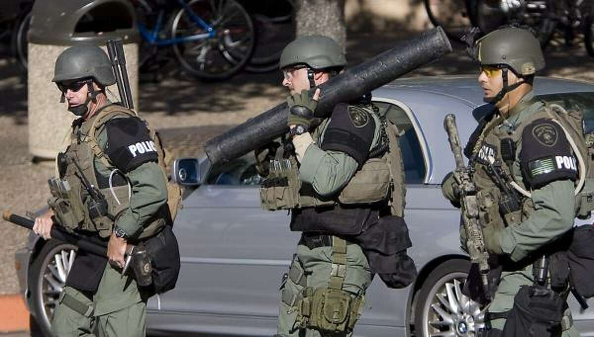 Austin law enforcement officials, one holding a battering ram, center, head out to buildings surrounding the Perry-Castaneda Library on the University of Texas campus Tuesday.