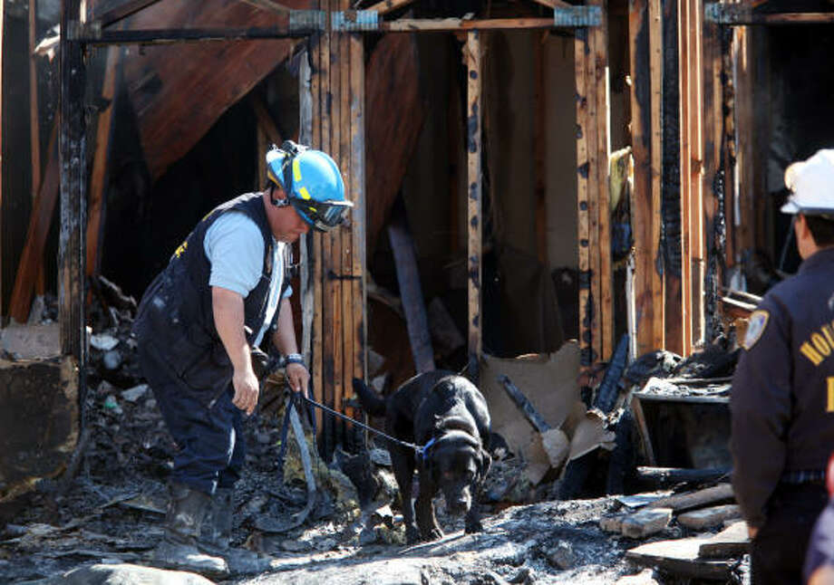 Arson Investigator walks the dog through the debris in efforts to find missing elderly couple after two alarm fire broke out at the Greenhouse Patio apartments in Houston, TX.  Firefighters extinguished the blaze, and stabilized the building to search for the elderly couple. Photo: Mayra Beltran, Chronicle