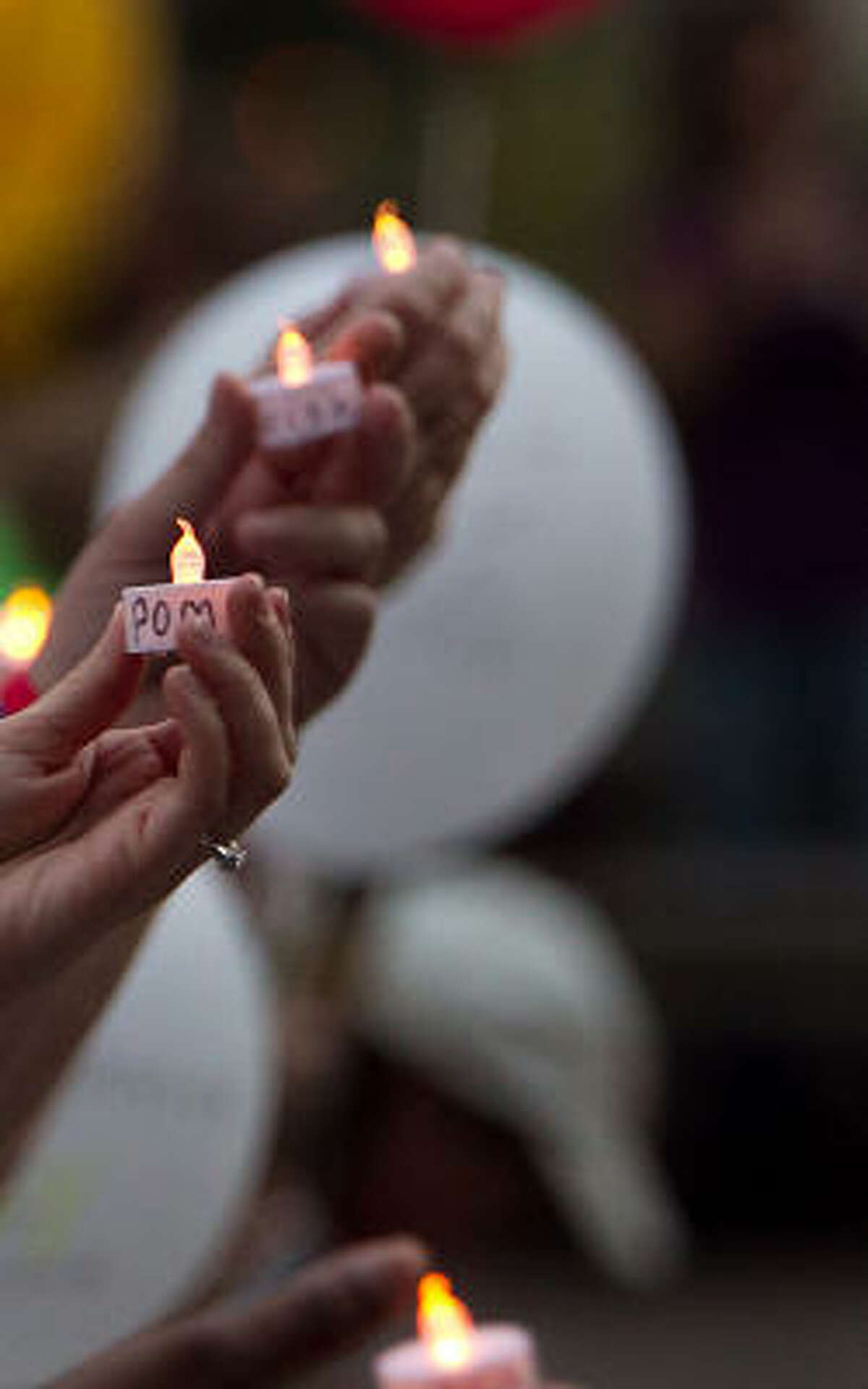 Candles are held up as the Houston Chapter of Parents of Murdered Children hold a candlelight vigil to recognize the National Day of Remembrance.