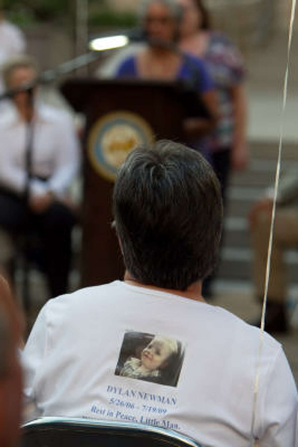 A woman wears a shirt in remembrance of a Dylan Newman who was murdered in July of 2009.