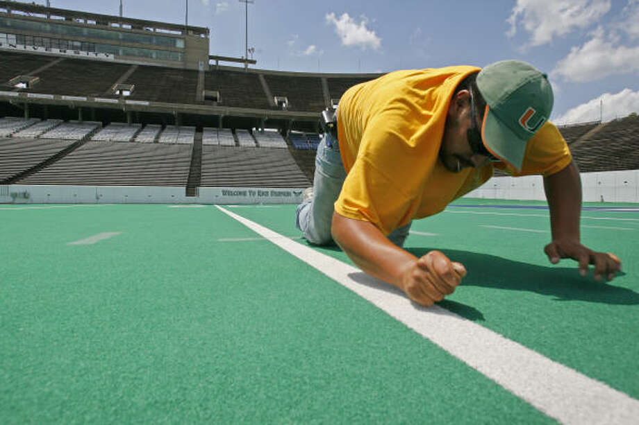 Jose Fontanez of RS Global cuts apart the old Astroturf at Rice Stadium on April 20, 2006. The old turf was later replaced with the more modern FieldTurf Duraspine. Photo: Ben DeSoto, Chronicle