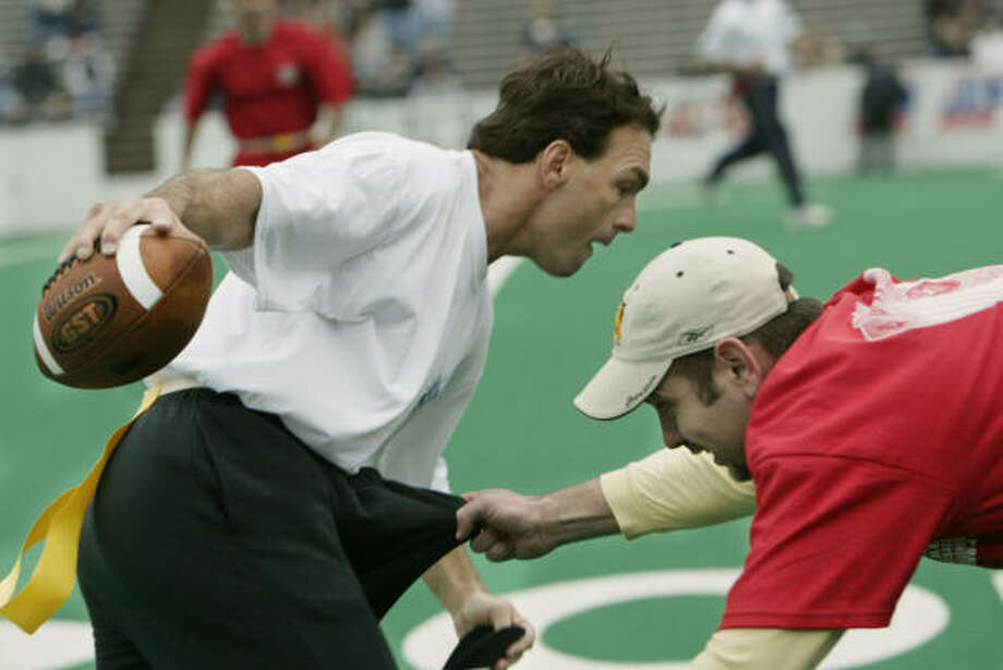 Former Boston College and later NFL quarterback Doug Flutie, left, tries to elude Jimmy Plante of Houston during the Celebrity Flag Football Challenge on Jan. 31, 2004, at Rice Stadium. The challenge benefited the NFL Alumni-Kids Charities. Plante won a spot on Andre Ware's team after winning a chili cookoff contest. Photo: Kevin Fujii, Chronicle