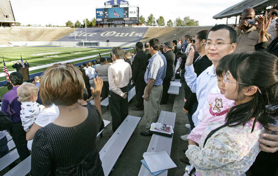 Feng (Michael) Li, originally from China, is  accompanied by his wife, Yan F. Huang, and daughter Cynthia Li Huang, 21 months. as he is sworn in as a U.S. citizen. Feng Li, a project manager with NASA, was one of an estimated 1,240 people who underwent a naturalization ceremony at Rice Stadium on Oct. 4, 2008. The ceremony had been postponed because of Hurricane Ike. Photo: Craig Hartley, For The Chronicle