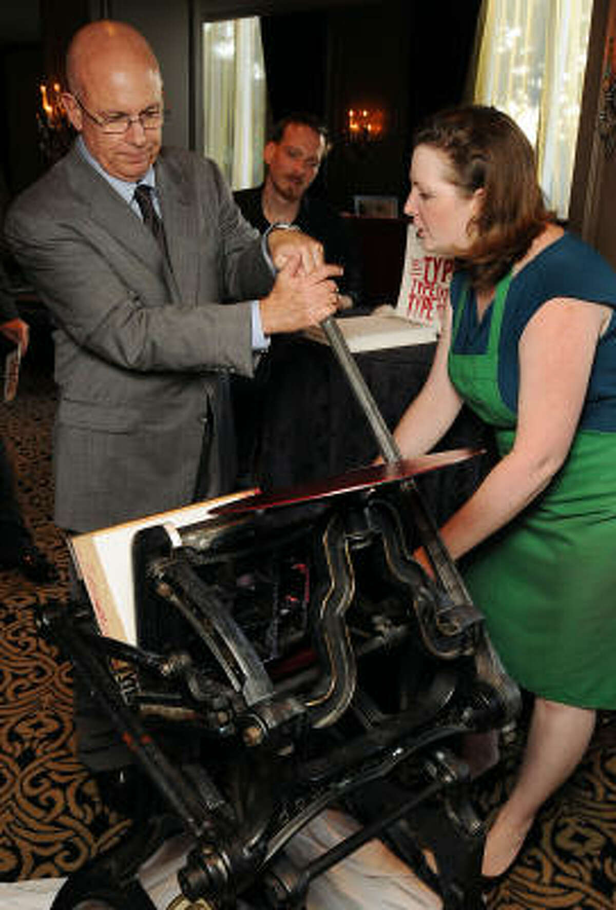 Brenda Cooper shows John Lehman how to run an early 20th-century printing press.