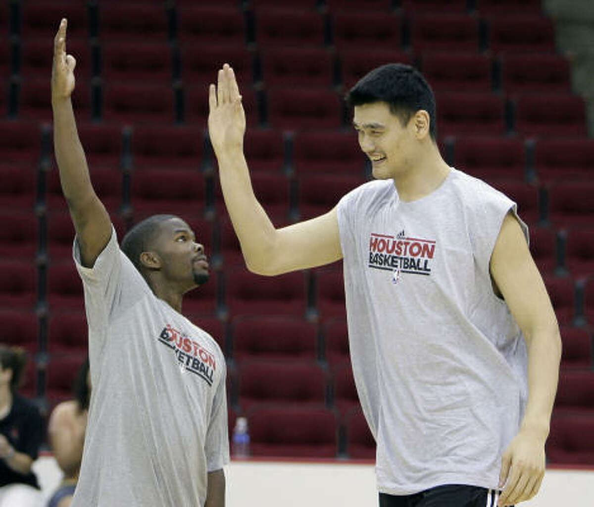 Rockets guard Aaron Brooks, left, high fives Yao Ming.