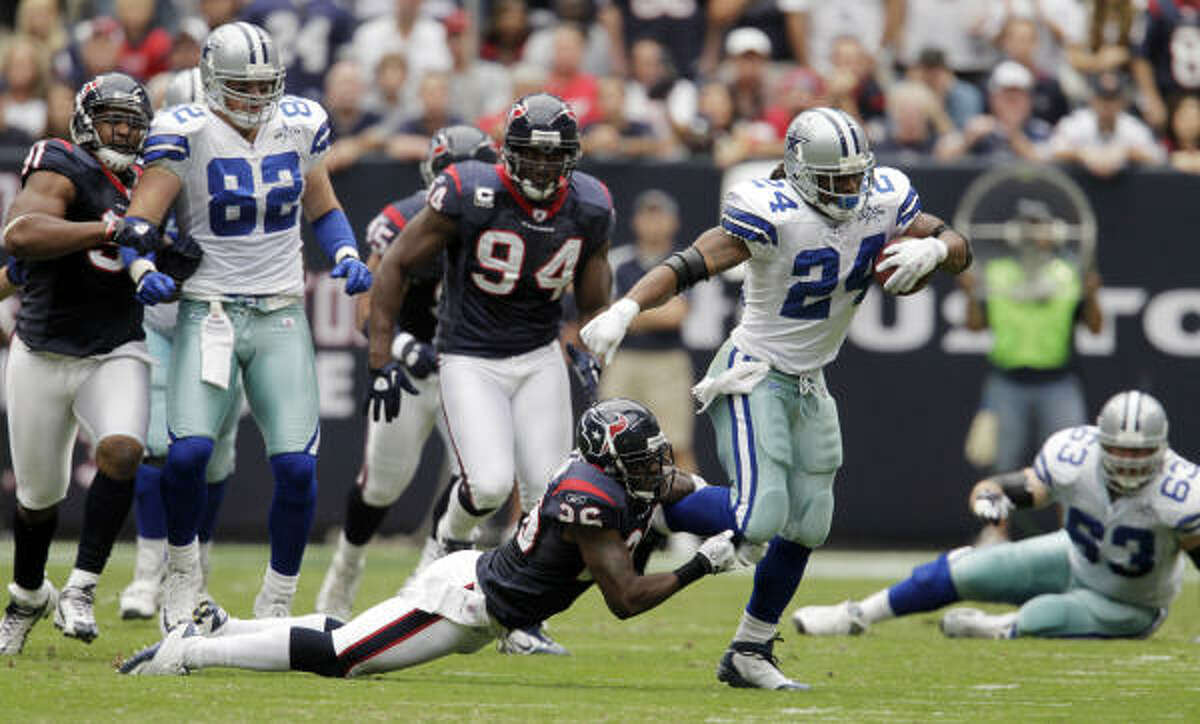Texans safety Eugene Wilson hangs onto Cowboys running back Marion Barber during the first quarter.
