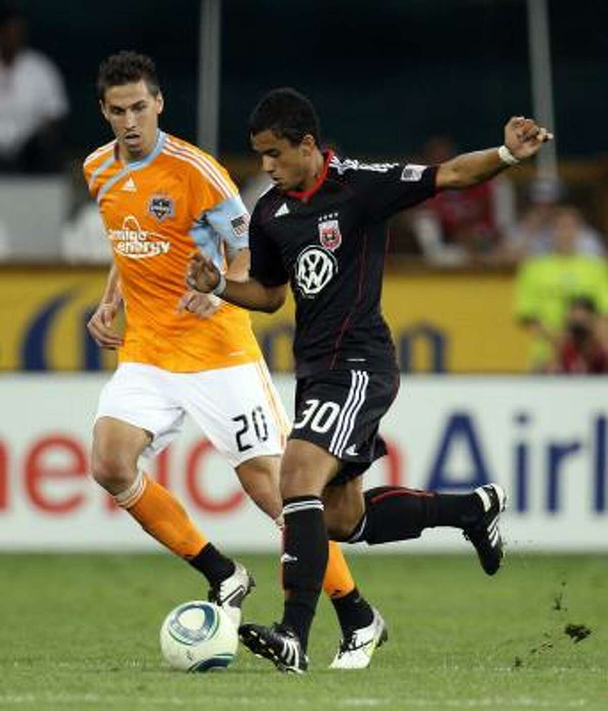 Junior Carreiro of D.C. United controls the ball against Geoff Cameron of the Dynamo.