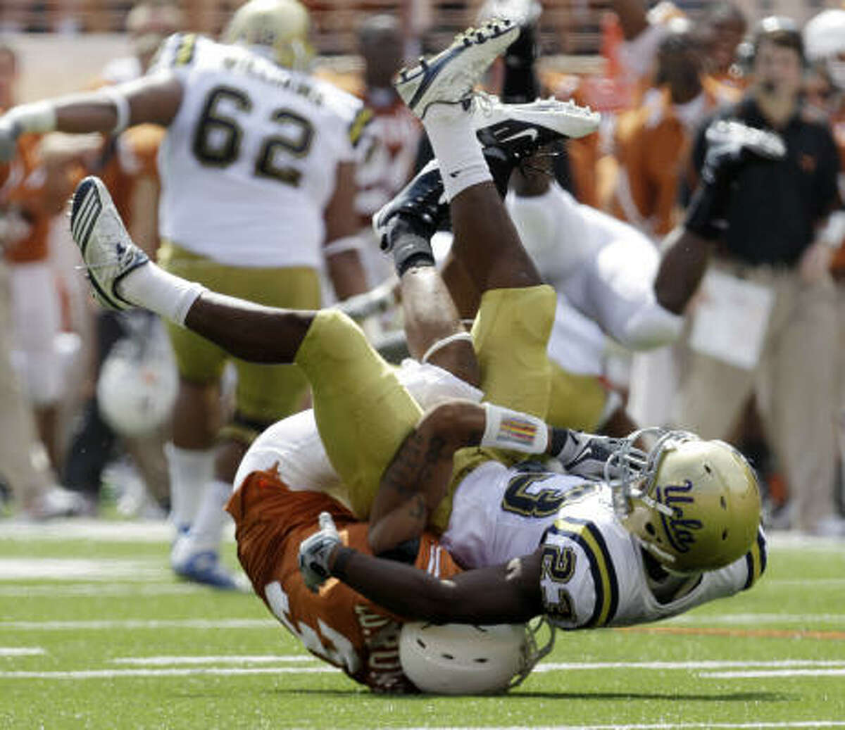 UCLA's Jonathan Franklin is upended by Texas' Curtis Brown during the second quarter.