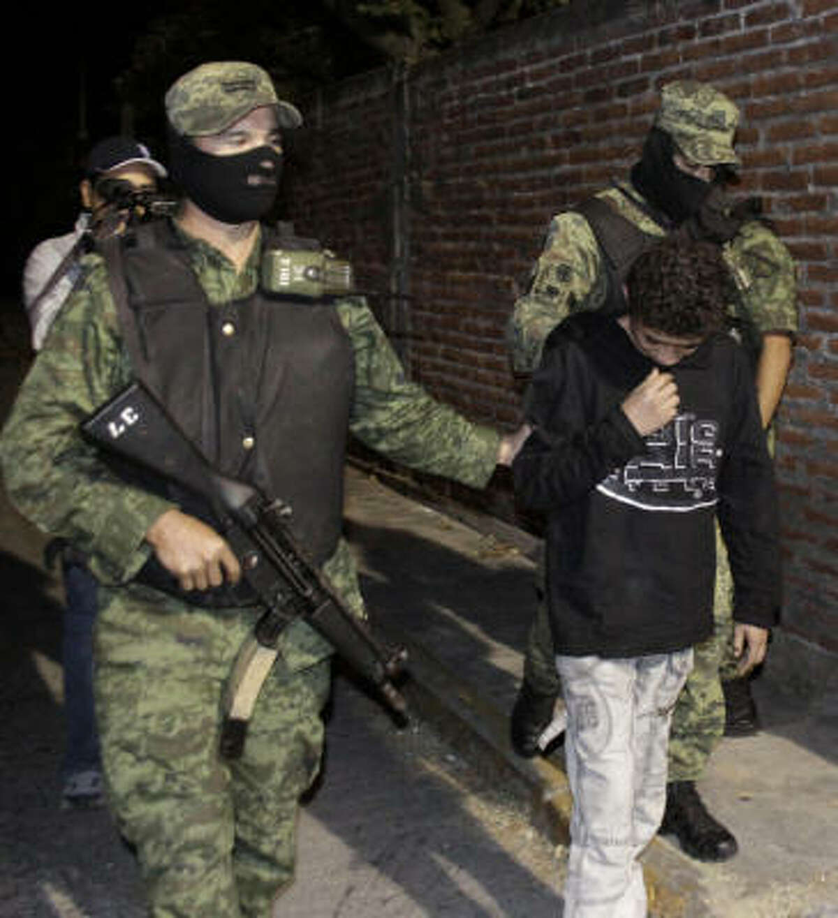"""Edgar Jimenez, 14, under guard Friday after his arrest near Cuernavaca, is suspected of being an infamous killer known as """"The Stoner."""""""