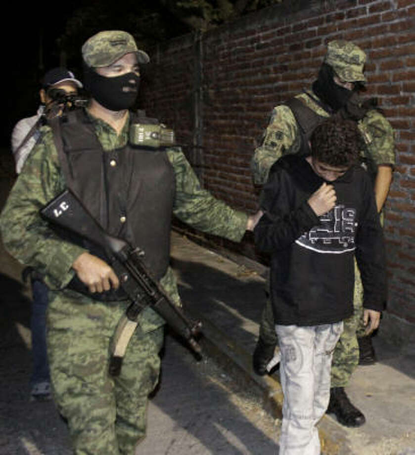 "Edgar Jimenez, 14, under guard Friday after his arrest near Cuernavaca, is suspected of being an infamous killer known as ""The Stoner."" Photo: Antonio Sierra, Associated Press"