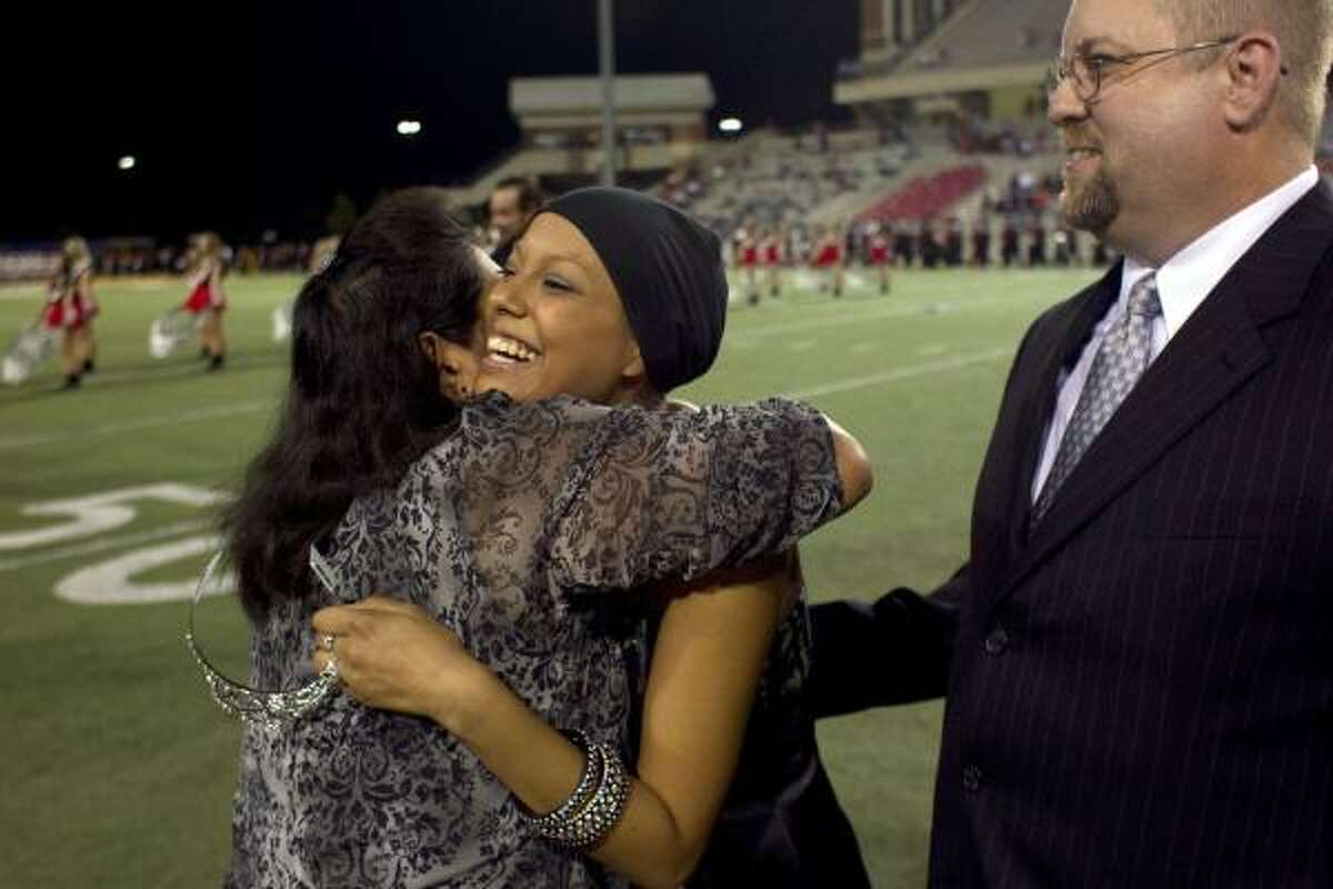 Next to her father Michael, Devin Duncan, 17, is hugged by her mother Debbie after Devin was crowned the homecoming queen during the halftime of the football game at the Berry Stadium. Devin, a senior at Langham Creek High School is currently receiving treatment for leukemia for a second time after surviving the disease when she was three.